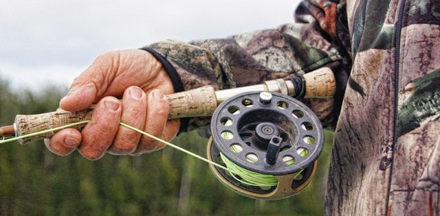 Man holding a fly fishing rod and reel