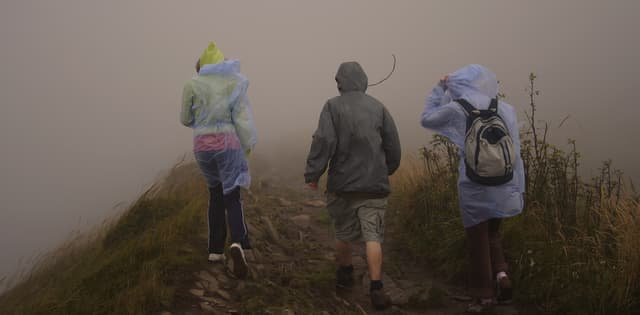three people hiking in rainy weather