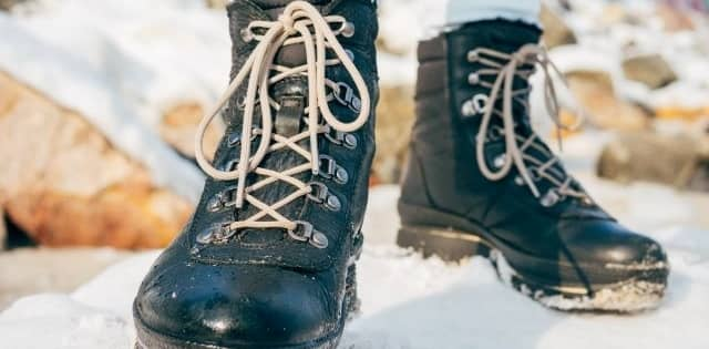 laced black winter boots in snow