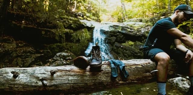 man resting on log with shoes and socks