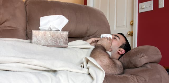 man lying on couch under a blanket sneezing into a tissue