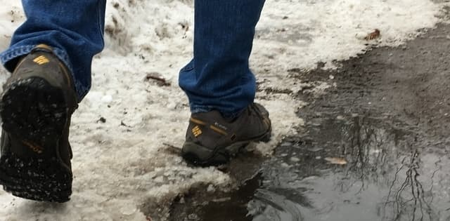 person wearing hiking shoes walking beside a slushy puddle