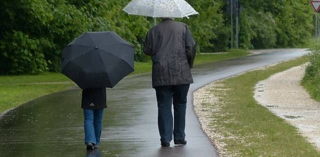 a couple walking in the rain with umbrellas