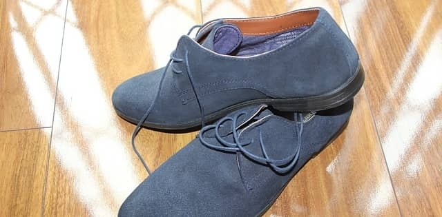 A pair of blue suede shoes on a hardwood floor
