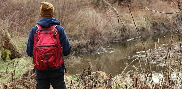 Man hiking outside standing by a pond