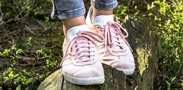Girl standing on log wearing pink suede shoes