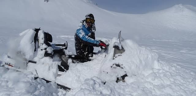 man stuck in the snow with snowmobile
