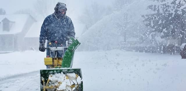 A man snow blowing his driveway