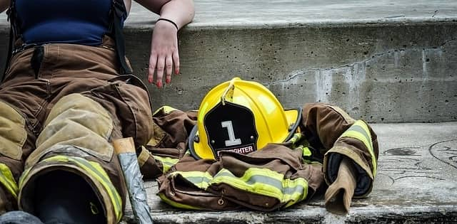 Woman Fire Fighter sitting on a concrete step
